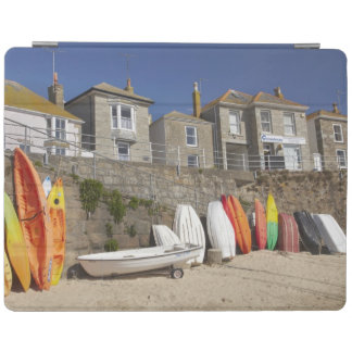 Kayaks and dinghies stacked against seawall at iPad cover
