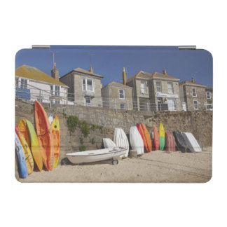 Kayaks and dinghies stacked against seawall at iPad mini cover
