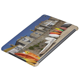 Kayaks and dinghies stacked against seawall at iPad air cover