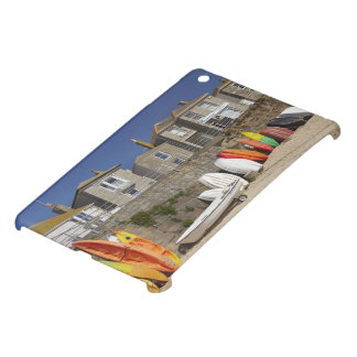 Kayaks and dinghies stacked against seawall at iPad mini case