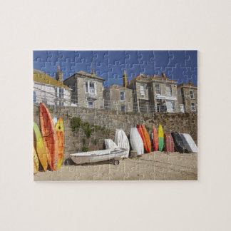 Kayaks and dinghies stacked against seawall at jigsaw puzzle