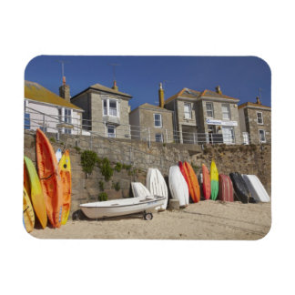 Kayaks and dinghies stacked against seawall at rectangular photo magnet