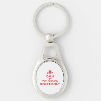 Keep Calm by focusing on Being Innocent Silver-Colored Oval Metal Keychain