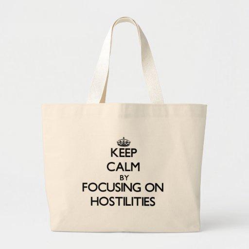 Keep Calm by focusing on Hostilities Canvas Bags