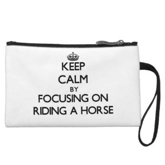 Keep Calm by focusing on Riding A Horse Wristlet Clutches