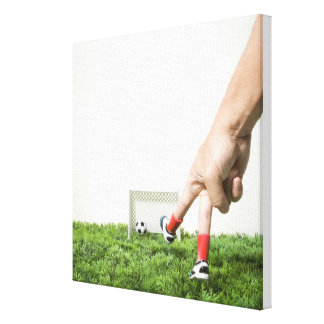 Kicking a soccer ball with finger imitating canvas print