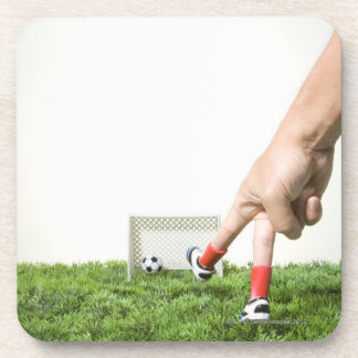 Kicking a soccer ball with finger imitating drink coaster