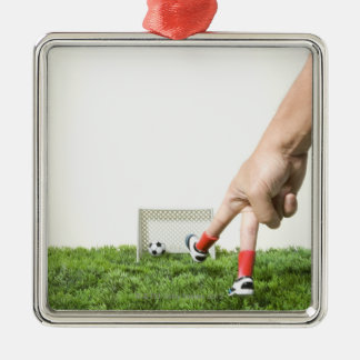 Kicking a soccer ball with finger imitating metal ornament