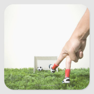 Kicking a soccer ball with finger imitating square sticker