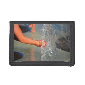 kid hands in water fountain trifold wallets