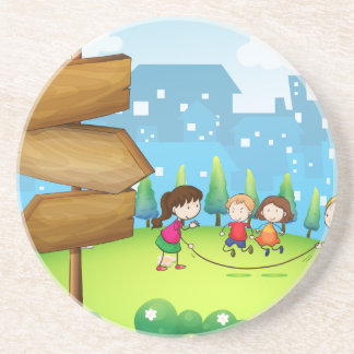 Kids playing in the hills with a wooden signboard drink coaster