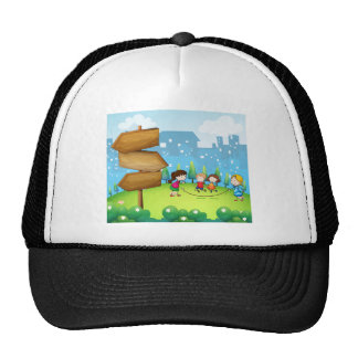 Kids playing in the hills with a wooden signboard trucker hat