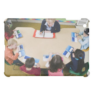 Kindergarten students sitting at table with iPad mini case