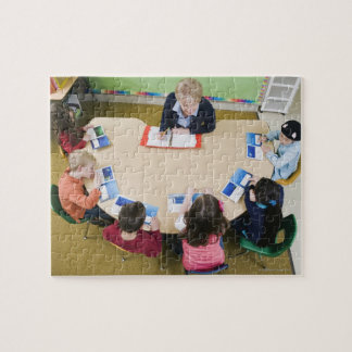 Kindergarten students sitting at table with jigsaw puzzle