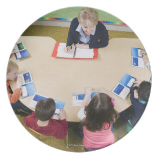 Kindergarten students sitting at table with melamine plate