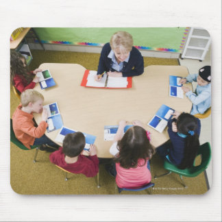 Kindergarten students sitting at table with mouse pad