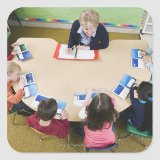 Kindergarten students sitting at table with square sticker