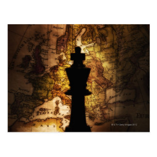 King chess piece on old world map postcard