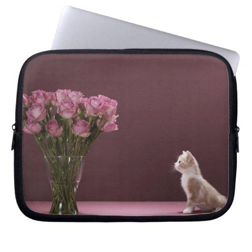 Kitten looking at vase of roses computer sleeves