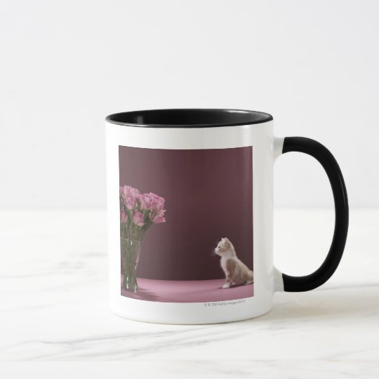 Kitten looking at vase of roses mug