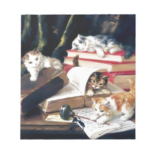 Kittens playing on a desk memo note pad