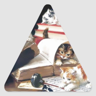 Kittens playing on a desk triangle sticker