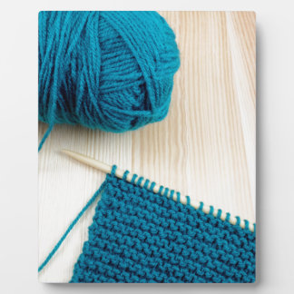 Knitting with teal yarn plaque
