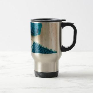Knitting with teal yarn travel mug