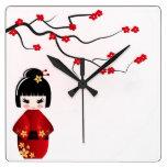Kokeshi doll under sakura branch wall clock