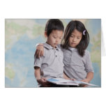 Korean children reading book near map greeting card