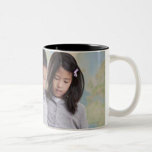 Korean children reading book near map coffee mug