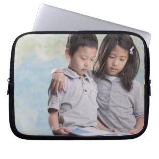 Korean children reading book near map laptop sleeve