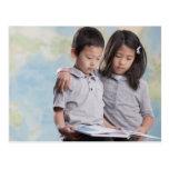 Korean children reading book near map post cards