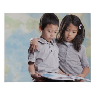 Korean children reading book near map poster