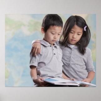 Korean children reading book near map poster
