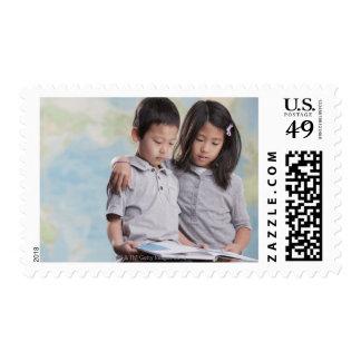 Korean children reading book near map stamp