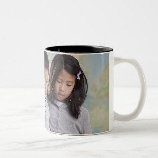 Korean children reading book near map Two-Tone coffee mug