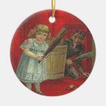 Krampus que juega con el chica adorno navideño redondo de cerámica