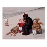 Krampus que juega con nieve de los niños postales
