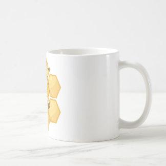 La abeja sonriente sostiene un cubo taza básica blanca