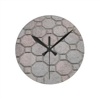 La acera del cemento teja el reloj