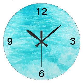 La agua de mar de las azules turquesas con salpica reloj redondo grande