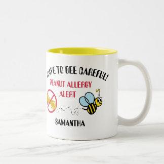 La alarma de la alergia del cacahuete manosea la taza de café de dos colores