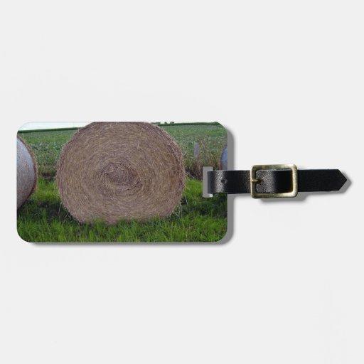La bala de heno rueda en un campo verde etiqueta para equipaje