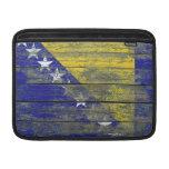 La bandera bosnio en la madera áspera sube a funda  MacBook