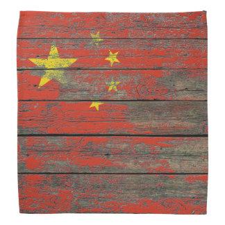 La bandera china en la madera áspera sube a efecto bandanas