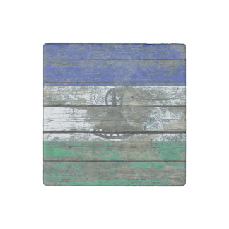 La bandera de Lesotho en la madera áspera sube a Imán De Piedra