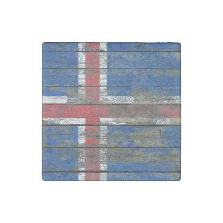 La bandera islandesa en la madera áspera sube a imán de piedra