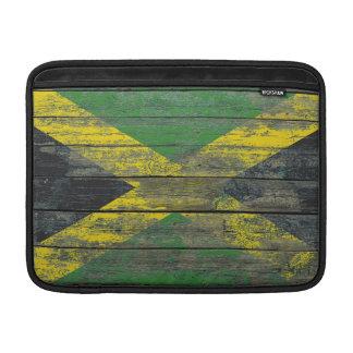 La bandera jamaicana en la madera áspera sube a fundas MacBook