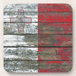 La bandera maltesa en la madera áspera sube a posavasos de bebidas
